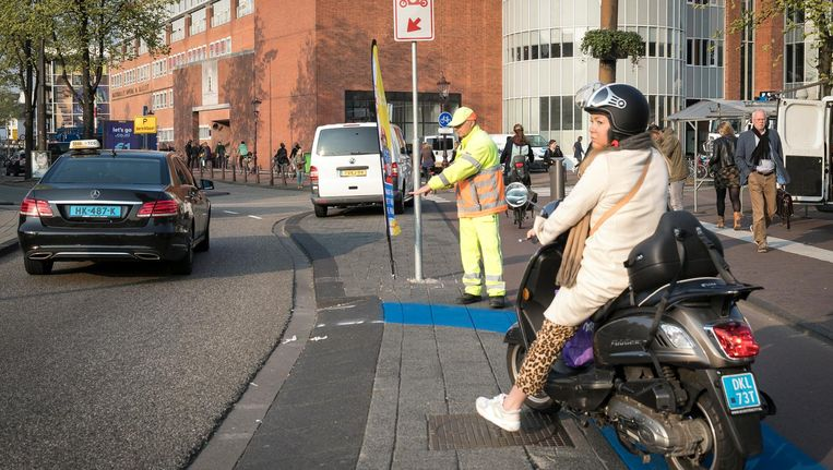 Bij het Waterlooplein in Amsterdam staan handhavers om snorfietsers de weg te wijzen Beeld Dingena Mol