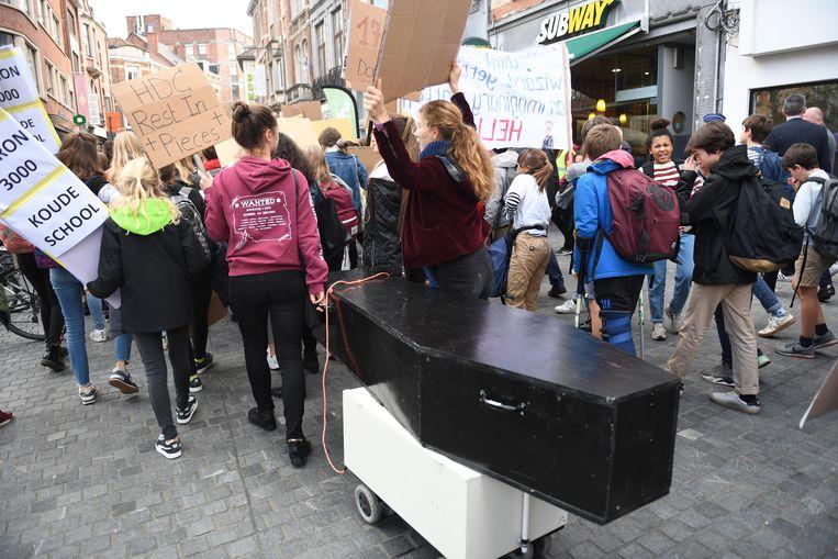 Scholieren betogen in Leuven tegen Perron 3000. De doodskist laat geen twijfel bestaan over de mening van de leerlingen en de leerkrachten die deelnamen aan de betoging.