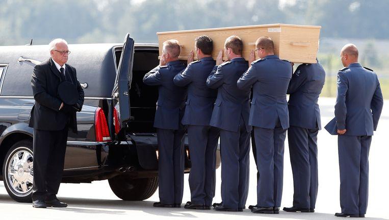 Militairen brengen lijkkisten naar gereedstaande rouwwagens op vliegbasis Eindhoven Beeld anp
