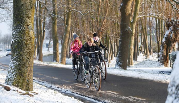 Kinderen op de fiets door de sneeuw in de buurt van Rotterdam.