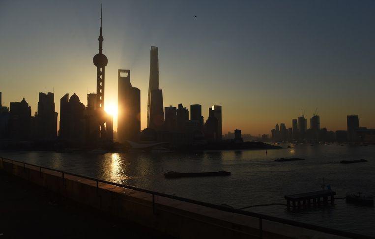 De zon komt langzaam op boven de skyline van Sjanghai. Beeld afp