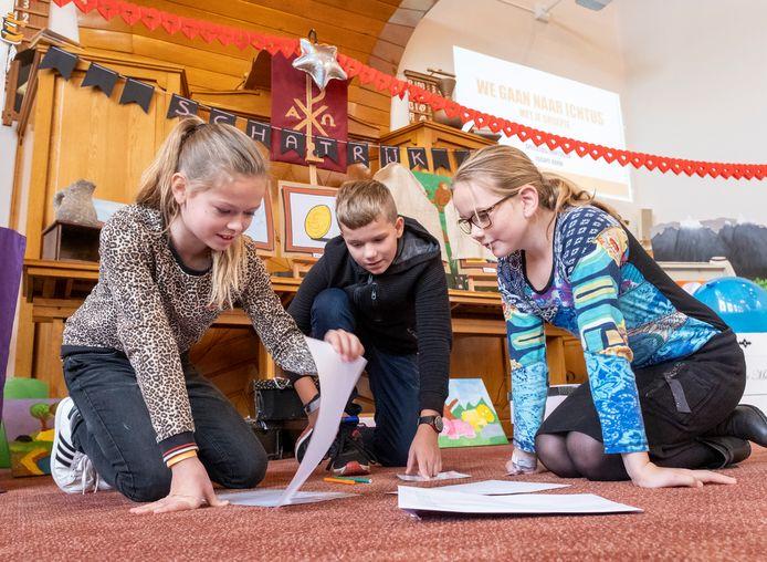 De 11-jarige deelnemers Jasmine, Jonathan en Janneke (vlnr) buigen zich over een escapespel op de grond in de kerk