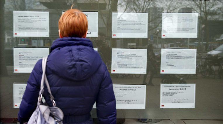 Een vrouw bekijkt vacatures aan een uitzendbureau.