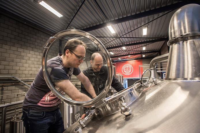 Niels de Vos van Bierbrouwerij Breda bekijkt samen met brouwer Joppe de Bres (rechts) een van de ketels.