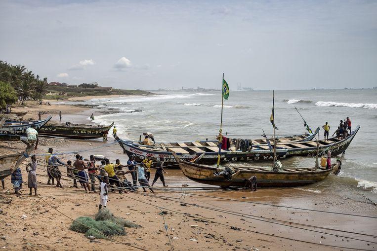 Jongeren uit Ghana slepen een boot uit het water. Beeld Sven Torfinn / de Volkskrant