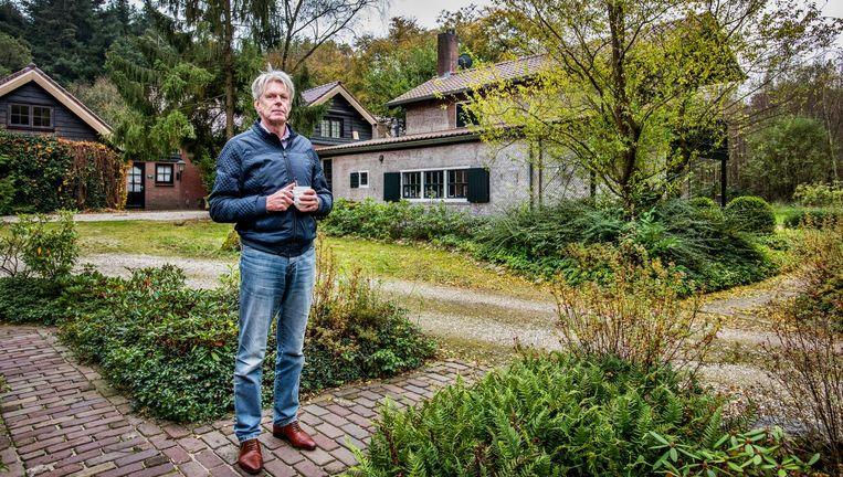 Gert Griffioen bij zijn huis (rechts). Linksachter staat het huis van de buurman. Beeld Raymond Rutting / de Volkskrant