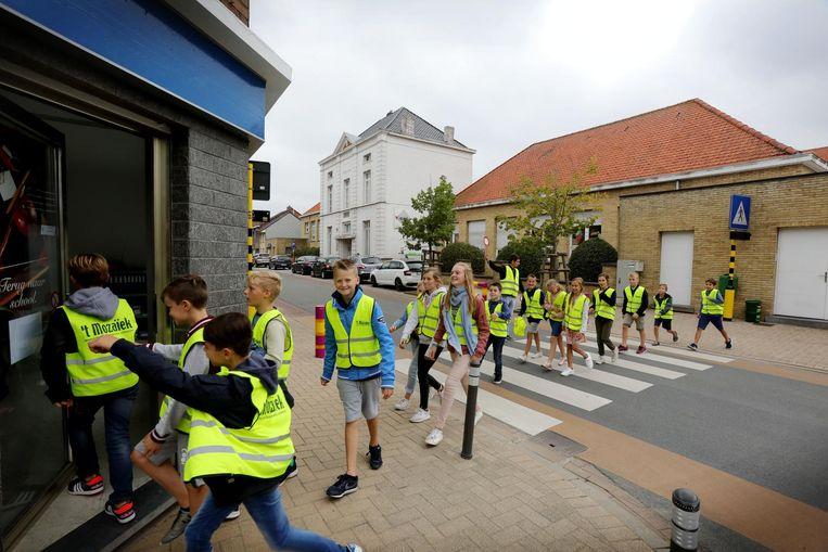 De leerlingen steken de straat over in hun fluohesjes.