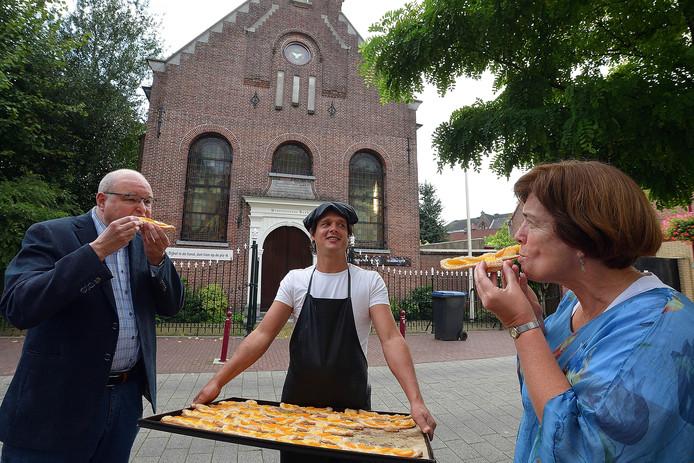 Tegen het decor van de protestantse kerk laten pastoor Maickel Prasing en dominee Charlotte Inkelaar zich de 'PKN-duif' goed smaken. In het midden bakker Jan Nagelkerke.