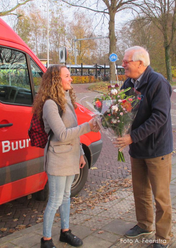 Buurtbuschauffeur Gosse Elzerink overhandigt de Lemelerveldse scholiere Selma Pot een bos bloemen als tienduizendste passagier van lijn 518.