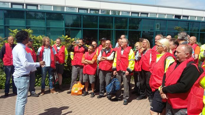 Werknemers van Scania luisteren naar vakbondsman Marijn van der Gaag van FNV. Ze hebben het gehad met het vele overwerk en voeren actie bij het kantoor in Zwolle.