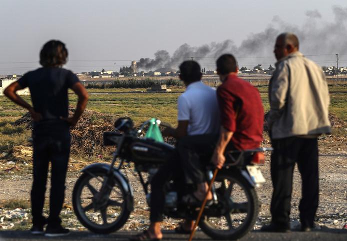 Mensen kijken bij de Turks-Syrische grens naar de rookpluimen die het resultaat zijn van het oorlogsgeweld.