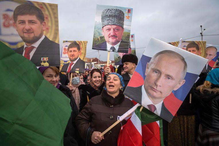 Een menigte loopt in 2016 door de Tsjetsjeense hoofdstad Grozny met portretten van de Russische president Vladimir Poetin en wijlen president Achmat Kadyrov (met hoofddeksel) om – op instigatie van het regime – steun te betuigen aan de huidige Tsjetsjeense president, Ramzan Kadyrov (met medailles).   Beeld AFP