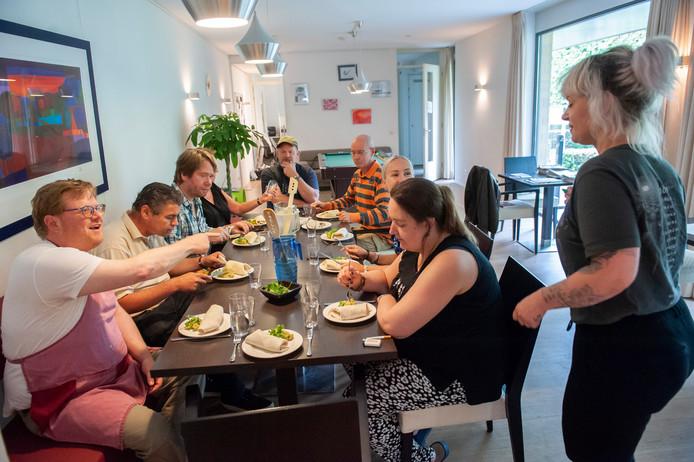 Bewoners en begeleiders in de huiskamer van Symfonie waar gezamenlijk gegeten kan worden.