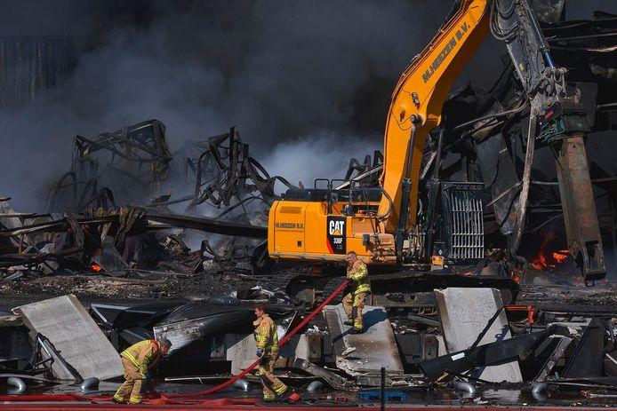 Brand in Hapert: resten worden weggehaald om brandende delen te kunnen blussen.