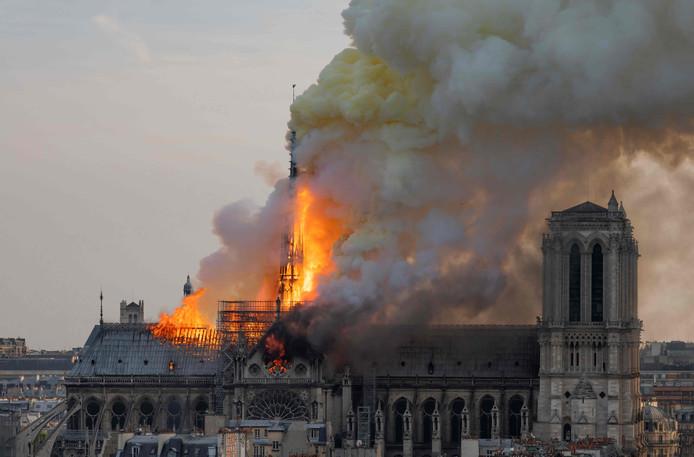 De spits en het dak gaan in vlammen op. Niet veel later zal de spits knakken: een beeld dat veel voorpagina's zal halen.