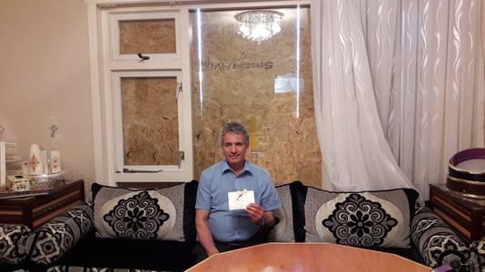 Omar met de trouwkaart van zijn dochter, voor de dichtgetimmerde ruit die is ingegooid in zijn huis in Duindorp.