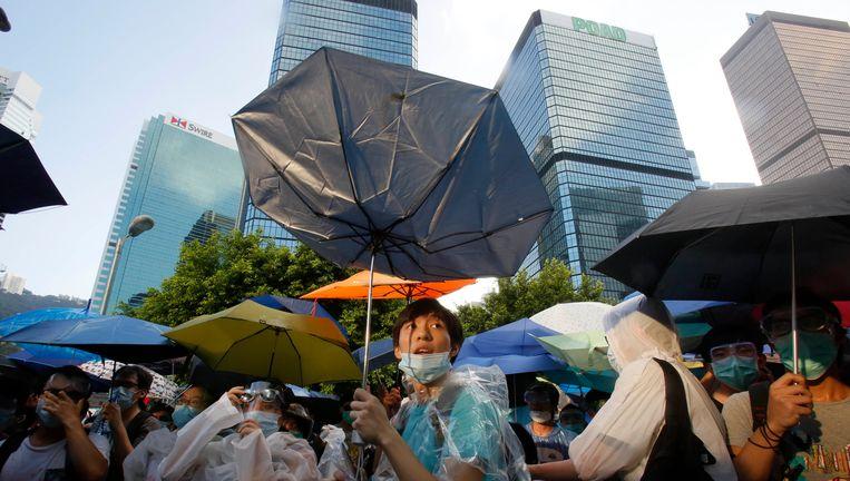 Pro-democratiedemonstranten proberen zich tegen traangas en peperspray te beschermen met paraplu's. Dat heeft de anti-China-acties in Hongkong de bijnaam 'paraplu-revolutie' opgeleverd. Beeld AP