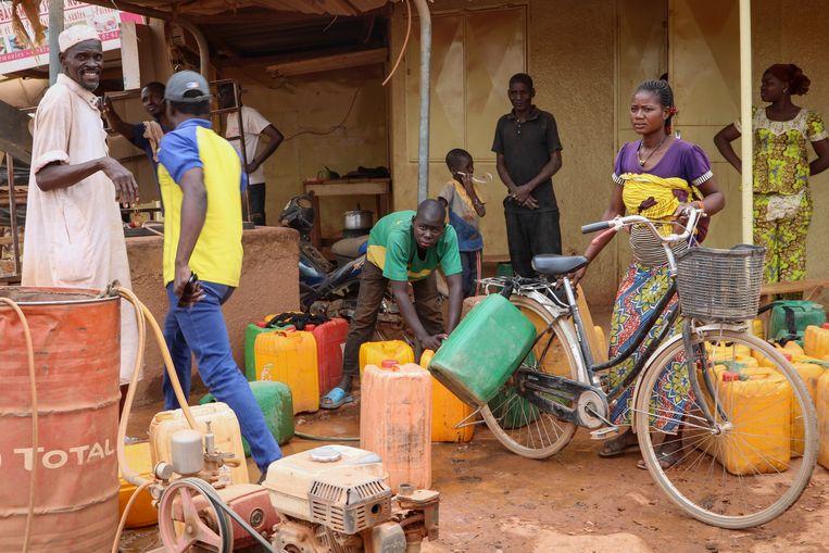 In een buitenwijk van de hoofdstad Ouagadougou van Burkina Faso halen bewoners bij een van de schaarse waterpunten water om te koken, te drinken en handen te wassen. Beeld AP / Sam Mednick