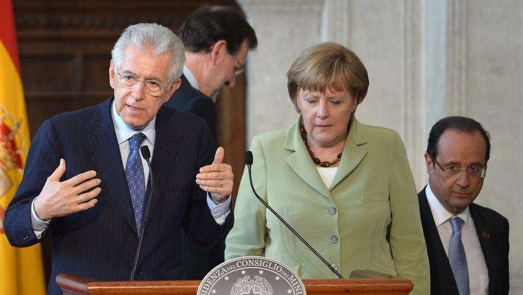 De Italiaanse premier Mario Monti naast de Duitse bondskanselier Angela Merkel, op de achtergrond de Spaanse premier Rajoy en de Franse president Hollande, vrijdag tijdens een ontmoeting in Rome Beeld ANP
