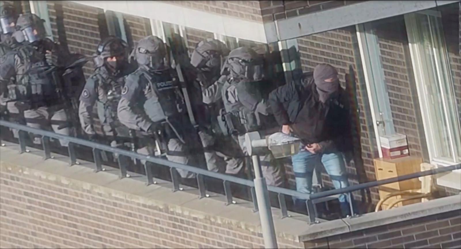 Een still uit camerabeelden van de politie tijdens een inval in een van de huizen van de verdachten in Arnhem.