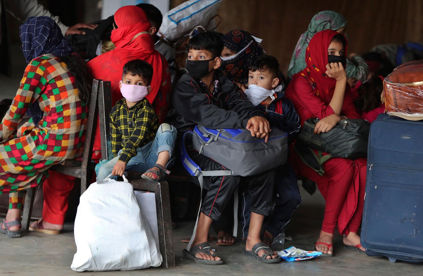 Kinderen met mondkapjes op wachten op de bus in Jammu. Dit straatbeeld in India zal voor enige tijd verdwijnen. De regering werkt aan de afkondiging van een uitgaansverbod.
