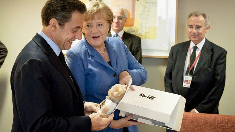Nicolas Sarkozy neemt het teddybeertje van het merk Steiff in ontvangst. Beeld ap
