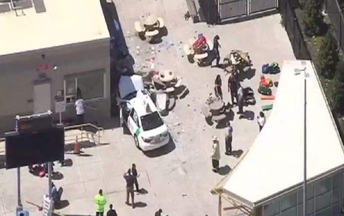 De taxi met zwaar beschadigde voorkant kwam na het incident tot stilstand tegen een gebouw.