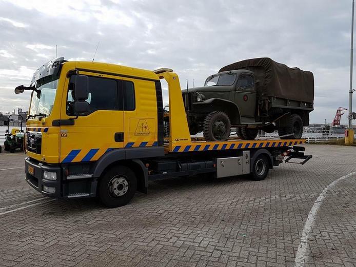 Het militaire voertuig op de bergingswagen.