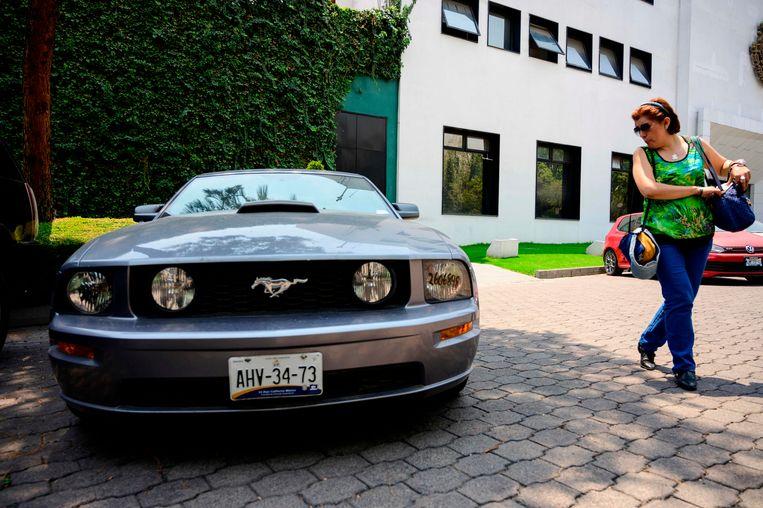 Een vrouw bekijkt een Ford Mustang die zondag geveild wordt.