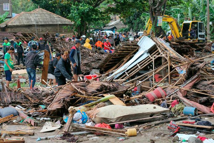 Inwoners van het getroffen gebied bekijken de ravage in Carita (Indonesië).