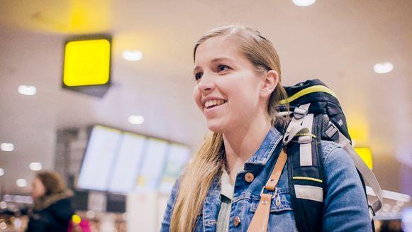 Runaway bride Emma komt glunderend toe op de luchthaven.