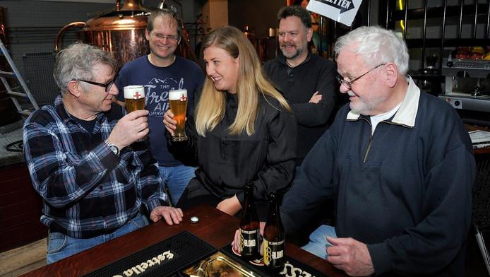 Pas na het brouwen mag er bier gedronken worden. Rachel proost met Cor Brons en zijn brouwmaten.