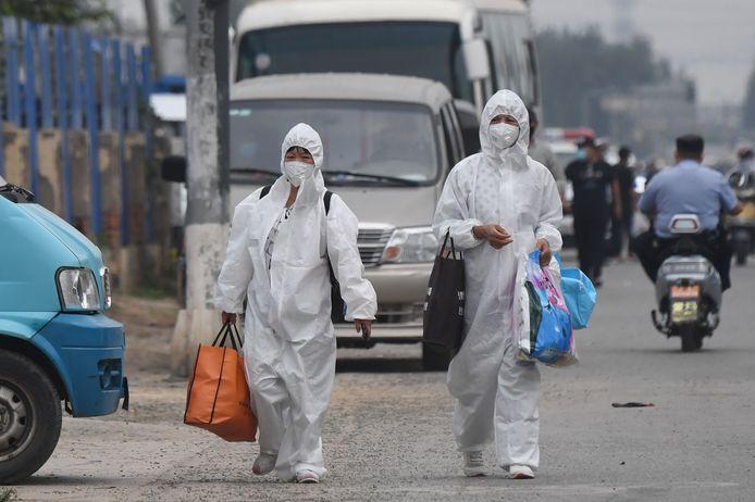 Vrouwen met beschermende kledij aan wandelen in de buurt van de Xinfadi-markt.