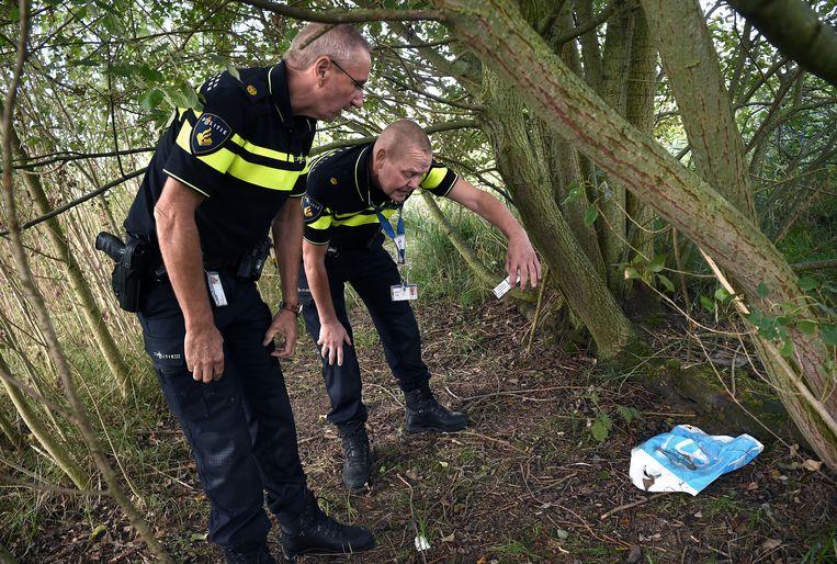 De politie zoekt naar Albanese migranten (in de buurt van een parkeerplaats voor truckers langs de snelweg) die via Nederland naar Engeland proberen te komen. Ze vinden een pakje Albanese sigaretten.  Beeld Marcel van den Bergh