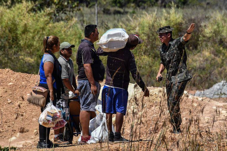 Een Braziliaanse soldaat praat met Venezolanen die de grens oversteken.