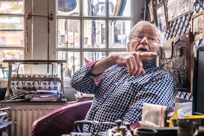 Koos Rozenburg op zijn vertrouwde plek bij het raam van zijn antiekzaak. ,,Er lopen hier mensen voorbij dat ik denk 'nou, nou'.''