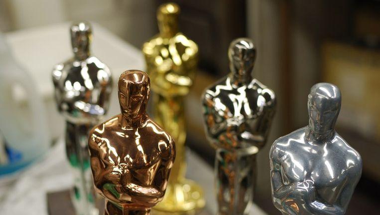Oscarbeeldjes in verschillende stadia van coating: koper, nikkel, zilver en 24-karaats goud. Beeld afp