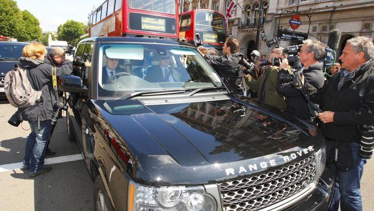 Fotografen en cameramannen omringen de auto van Rupert Murdoch in Londen. Beeld ap