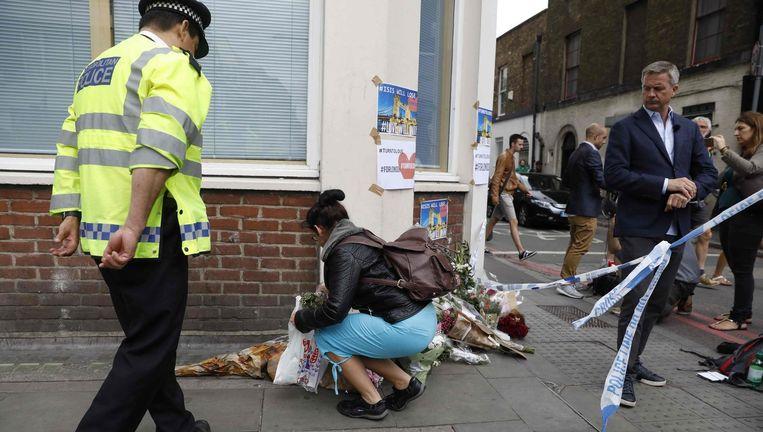 Een vrouw legt bloemen neer bij het politiecordon op Borough High Street Beeld afp