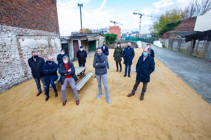 Leden van het gemeentebestuur en directieleden van de omliggende scholen op het pleintje naast de nieuwe doorsteek.