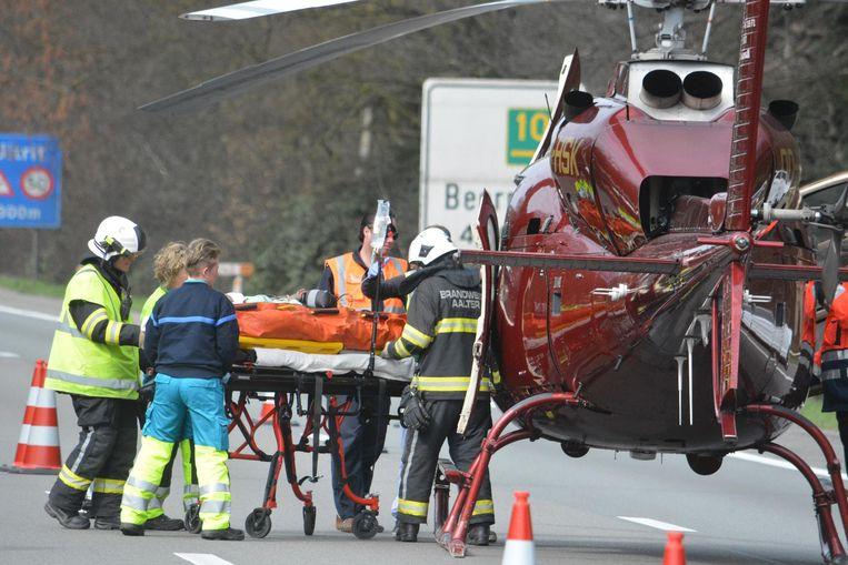 De hulpverleners brengen de gewonde moeder naar de MUG-heli op de snelweg. Rechts: de verhakkelde bestelwagen.