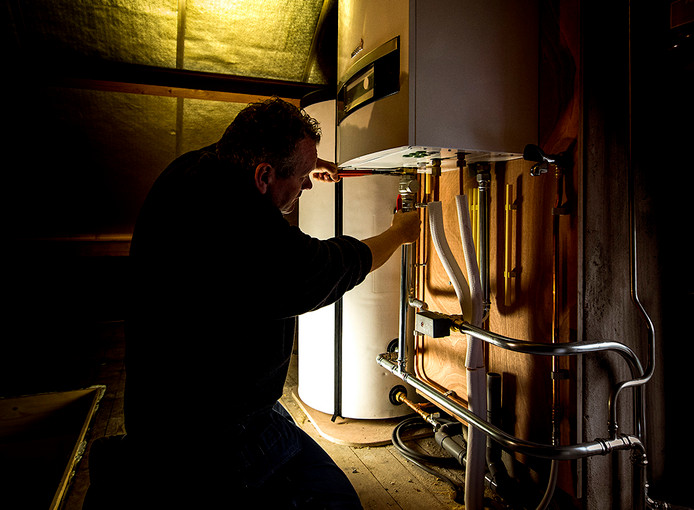 Foto ter illustratie. Een installateur sleutelt aan een Nefit-ketel.
