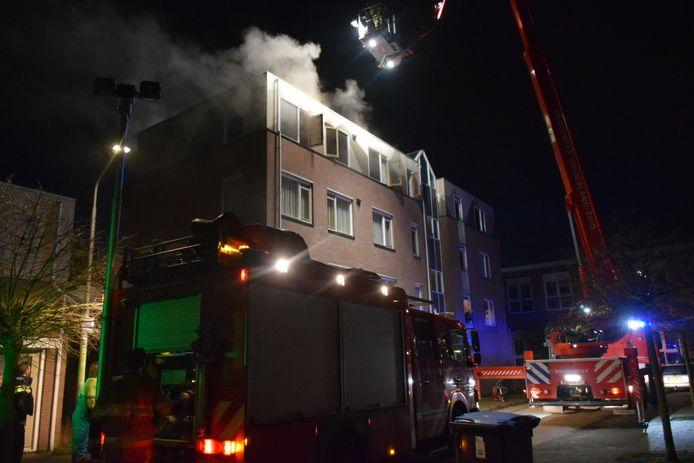 Met een hoogwerker blust de brandweer een brand in een appartement aan de Willem Barentszstraat in Nijmegen.