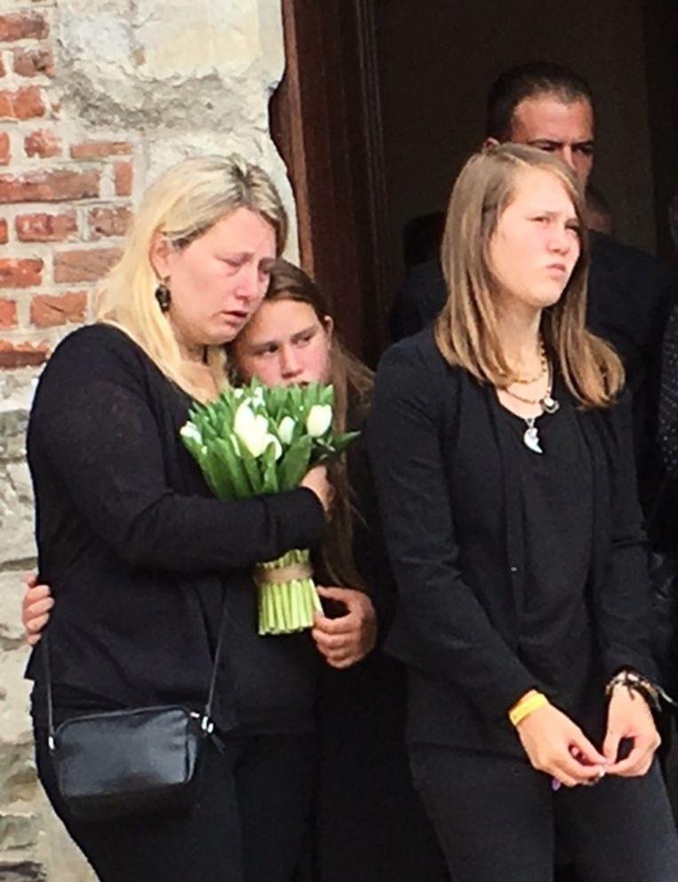 dPetra Bogaert (35), de partner van Frédéric (26), kijkt samen met dochters Charity (14) en Kynesha (13) hoe de kist wordt weggedragen.