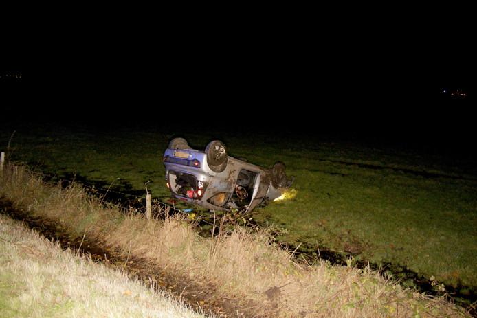 De auto van de man belandde op kop in het naastgelegen weiland.