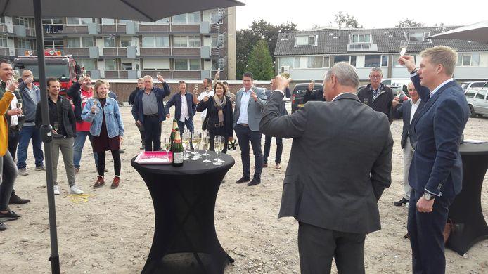Joost Konings (re) en wethouder Theunis heffen het glas op de nieuwbouw.