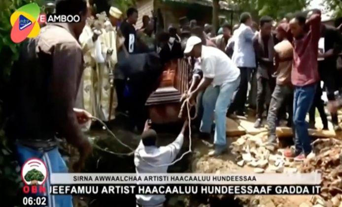 Videostill van het moment dat de kist waarin het lichaam van de vermoorde Ethiopische zanger Hachalu Hundessa ligt in het graf wordt gehesen.