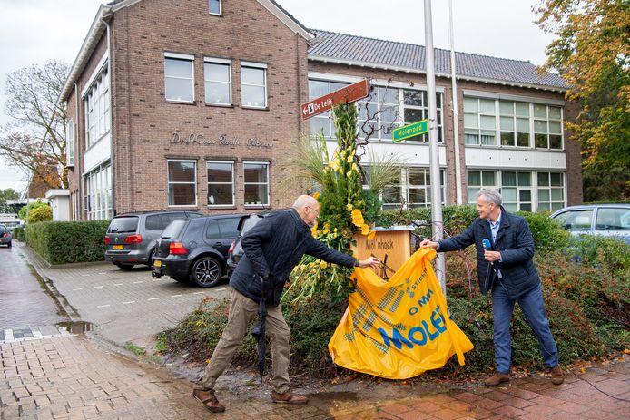 Na een toespraak op straat onthult wethouder Leo Bongers (r) een houten plaat met de naam Möl'nhoek, die verborgen zat onder de vlag van de stichting Ommer Molens. Johan Willemsen, een van de initiatiefnemers voor de nieuwe naam, helpt een handje.