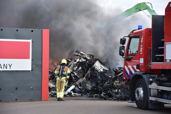 De brandweer bestrijdt het vuur bij het recyclingbedrijf.