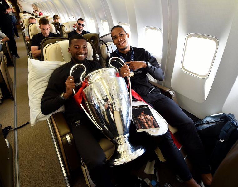 Wijnaldum en van Dijk met de beker van de Champions League in het vliegtuig naar Liverpool. Beeld RV